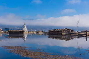 Houses on the water with the reflection of the white clouds and blue skyの写真素材 [FYI02860969]