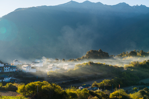 Sun and shadow through fog; trees; village; Meili Snow Mountain;Deqin;Yunnan; Chinaの写真素材 [FYI02861004]