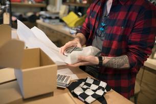 Motorcycle shop owner unwrapping merchandiseの写真素材 [FYI02861024]