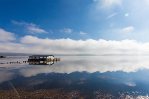 Lonely house stands on the water with the reflection of the skyの写真素材 [FYI02861048]