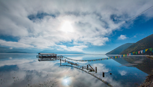 Sunlight through cloud; lake refection; cabin at the lake with pray flag line. Napa Hai Nature Reserの写真素材 [FYI02861067]