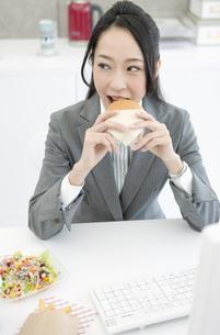 ハンバーガーを食べるビジネスウーマンの写真素材 [FYI02864479]