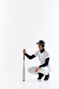 バットを持って座っている野球のユニフォームを着た男性の写真素材 [FYI02866491]