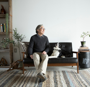 ソファで愛犬と過ごすシニア男性の写真素材 [FYI02866905]