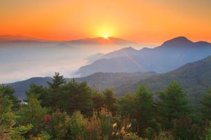 浅間山から昇る朝日と冠着山などの山並みと秋の樹林の写真素材 [FYI02867862]