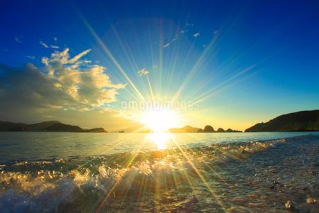 波しぶきと夕日と屋嘉比島など慶良間諸島の写真素材 [FYI02868270]