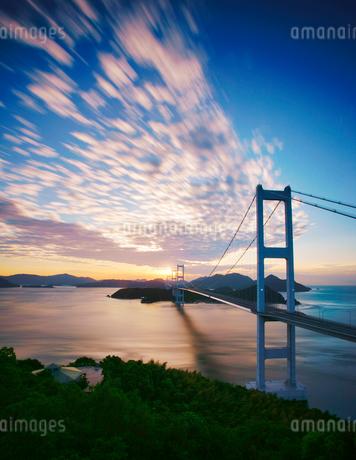 糸山公園展望台から望む来島海峡大橋と朝日と流れる雲の写真素材 [FYI02868752]