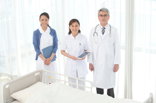 病院のベッドの前に立つ医者と看護師の写真素材 [FYI02869040]