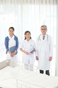 病院のベッドの前に立つ医者と看護師の写真素材 [FYI02869068]