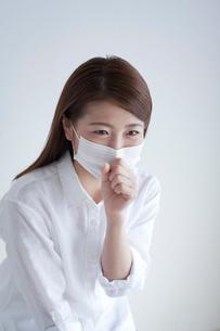 マスクをして咳き込む女性の写真素材 [FYI02869837]