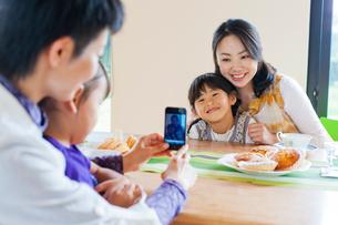 テーブルを挟んで写真を撮る2組の母と子の写真素材 [FYI02870226]
