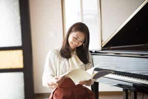 ピアノの前で楽譜を見ている女性の写真素材 [FYI02871849]
