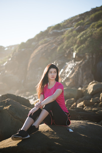 トレーニングウェアで岩の上に座っている女性の写真素材 [FYI02871936]