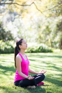 緑の中で瞑想をしている女性の写真素材 [FYI02872051]