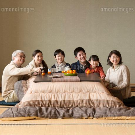 こたつでテレビを見る3世代家族の写真素材 [FYI02872866]