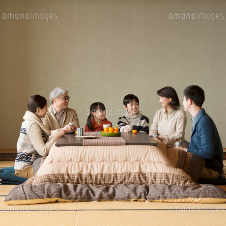 こたつで談笑をする3世代家族の写真素材 [FYI02872867]
