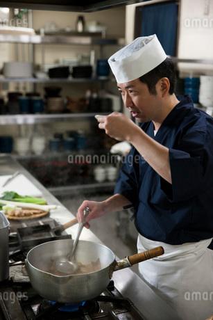 煮魚の味見をする調理師の写真素材 [FYI02873021]