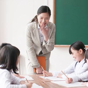 グループ学習をする小学生と先生の写真素材 [FYI02873090]