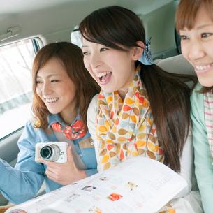 車の中で微笑む3人の女性の写真素材 [FYI02874745]