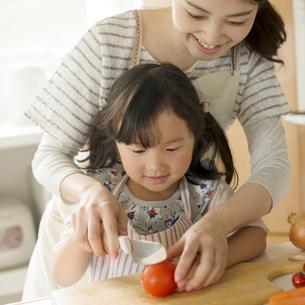 母親に野菜の切り方を教えてもらう女の子の写真素材 [FYI02874856]