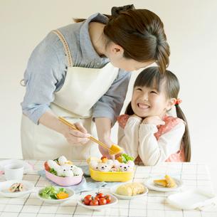 キャラクター弁当を作る母親と微笑む女の子の写真素材 [FYI02875050]