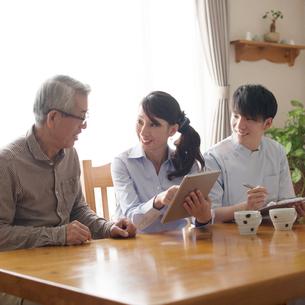 シニア男性と話をするケアマネージャーと介護士の写真素材 [FYI02875352]