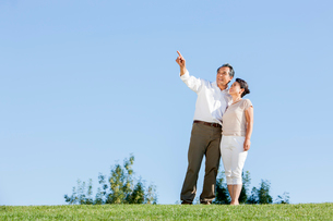 Happy mature couple looking at view in a parkの写真素材 [FYI02875924]