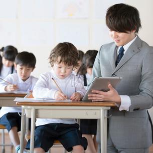 先生に勉強を教わる小学生の写真素材 [FYI02875985]