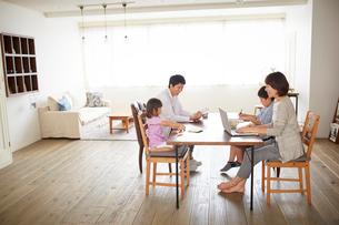 ダイニングでくつろぐ4人家族の写真素材 [FYI02876872]