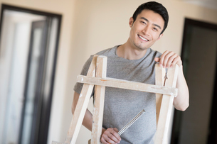 Young Chinese man working on home renovationの写真素材 [FYI02877075]