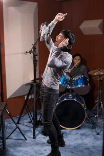 Young man singing in recording studioの写真素材 [FYI02877222]