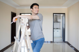 Young Chinese man working on home renovationの写真素材 [FYI02877279]