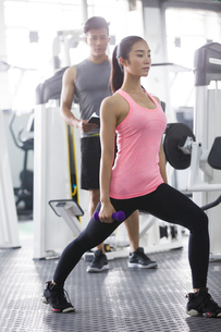 Young woman working with trainer at gymの写真素材 [FYI02877373]