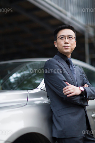 Mid adult businessman standing next to the carの写真素材 [FYI02877588]