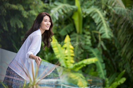 Happy young Chinese woman relaxing on balconyの写真素材 [FYI02877948]