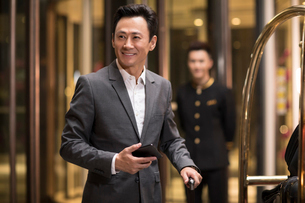 Cheerful Chinese businessman in hotel lobbyの写真素材 [FYI02878177]
