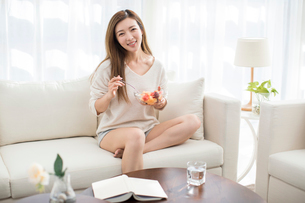 Cheerful young Chinese woman eating fruit salad on sofaの写真素材 [FYI02878256]