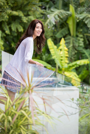 Happy young Chinese woman relaxing on balconyの写真素材 [FYI02878278]
