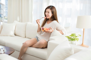 Cheerful young Chinese woman eating fruit salad on sofaの写真素材 [FYI02878293]