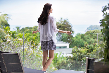 Happy young Chinese woman relaxing on balconyの写真素材 [FYI02878436]