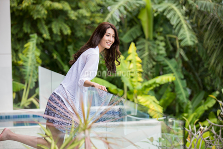 Happy young Chinese woman relaxing on balconyの写真素材 [FYI02878481]