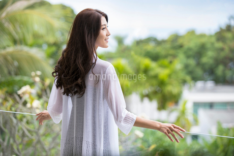 Happy young Chinese woman relaxing on balconyの写真素材 [FYI02878574]