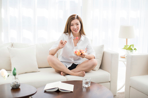 Cheerful young Chinese woman eating fruit salad on sofaの写真素材 [FYI02878676]