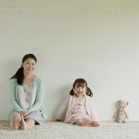 カーペットの上に座り微笑む親子の写真素材 [FYI02878708]