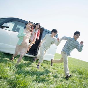 車から駆け出す若者たちの写真素材 [FYI02878722]