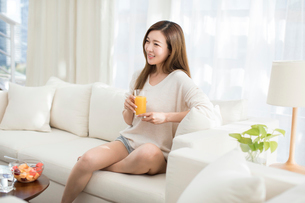 Cheerful young Chinese woman drinking juice on sofaの写真素材 [FYI02878732]