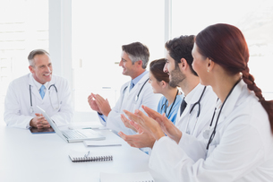 Doctors applauding a fellow doctorの写真素材 [FYI02878857]