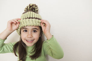 A young child with long brown hair wearing a knitted hatの写真素材 [FYI02878890]