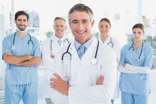 Smiling doctor with fellow doctorsの写真素材 [FYI02878902]