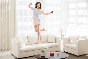 Cheerful young Chinese woman jumping and listening to music on sofaの写真素材 [FYI02878917]